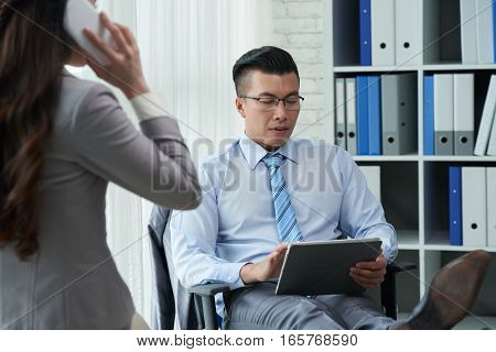 Vietnamese businessman sitting on chair and reading information on tablet computer