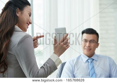 Smiling business lady pointing at screen of smartphone and showing in to coworker