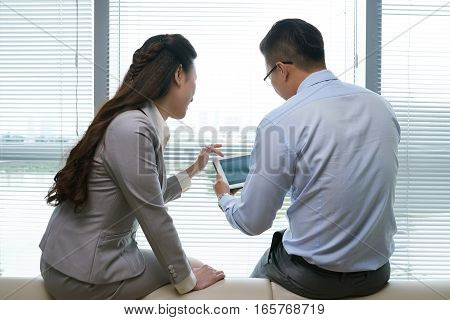 Rear view of business couple watching something on tablet computer
