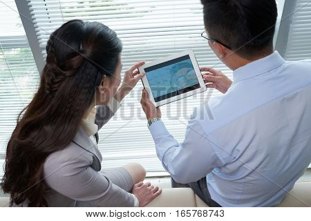 Businessman showing his calendar on tablet computer to female colleague, view from above