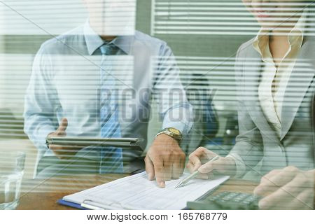 Asian business people discussing financial data in office