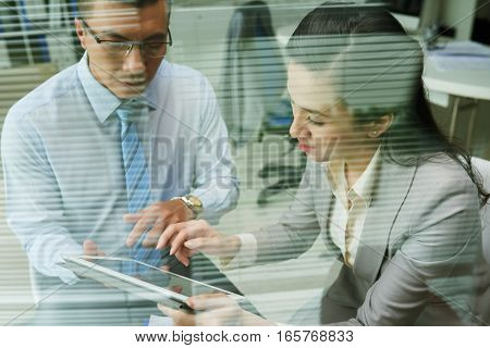 Business people reading information on digital tablet