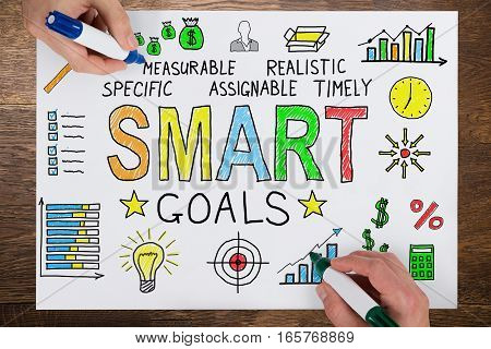 Two People Using Colorful Marker For Drawing Smart Goals Concept On White Paper