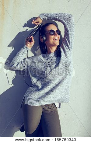 Woman listening music by headphones at wall enjoying sunshine