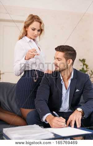 Hot secretary offering handcuffs for young CEO in office