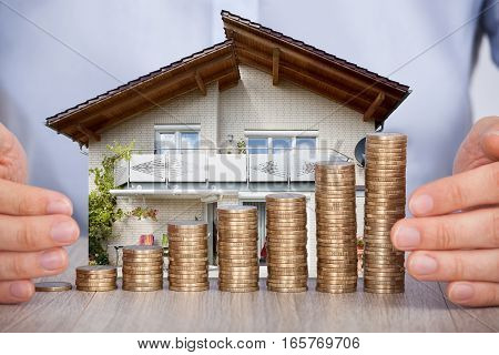 Close-up Of Man's Hand Securing House Model And Stack Of Coins On Wooden Desk