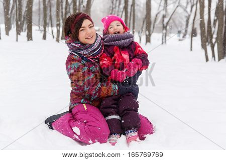 Mother and daughter sitting on snow in winter park