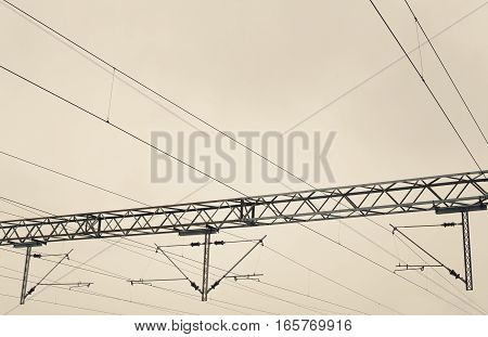 Abstract composition of railway electric wires, white cloudy sky in background.