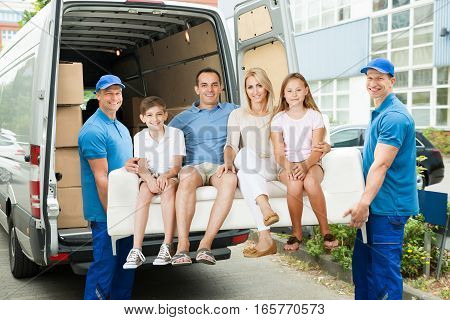 Two Male Happy Furniture Movers Carrying Family On Sofa Out Of Truck Outside The House.