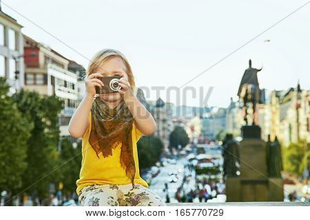 The spirit of old Europe in Prague. modern child on Wenceslas Square in Prague Czech Republic with digital camera taking photo