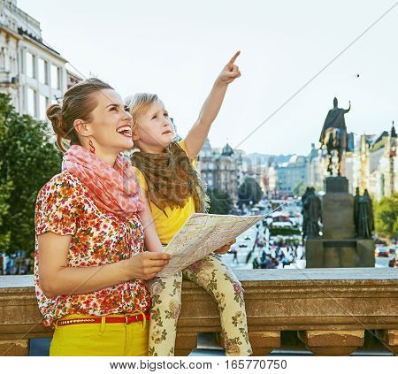 Mother And Daughter In Prague Holding Map And Pointing