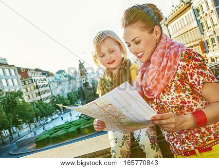 Mother And Daughter Tourists Looking At The Map In Prague