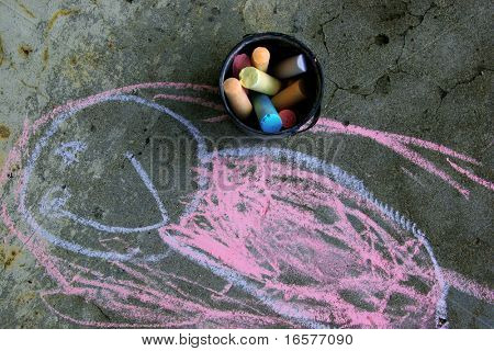 Bucket of chalk on pavement besides a drawing of a girl