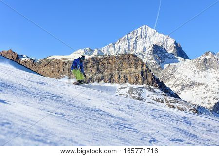 Male snowboarder on the slope with high mountain peaks on background
