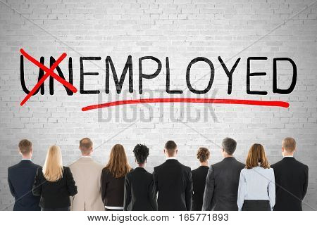 Businesspeople Looking At Unemployed Concept With Crossing Off Letters Un On Brick Wall. Job And Employment Concept