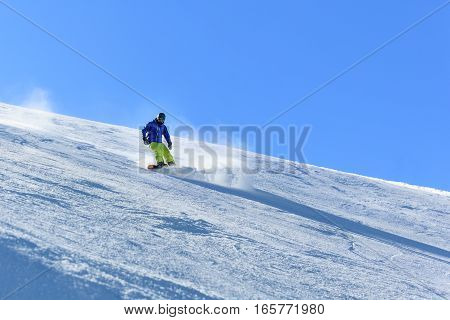 Male snowboarder on the slope sliding down the slope