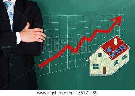 Close-up Of Businessperson Standing Beside Real Estate Growth Concept On Blackboard