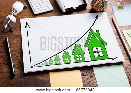 High Angle View Of Diagram Of Growth In Real Estate Prices On Wooden Desk
