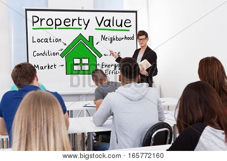 A Male Teacher Explaining The Concept Of Property Value Concept To Students In Classroom