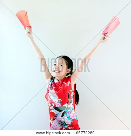 Happy chinese new year young asian girl in traditional dress (Cheongsam) holding red envelope with exciting and cheerful face standing on white background and copy space.