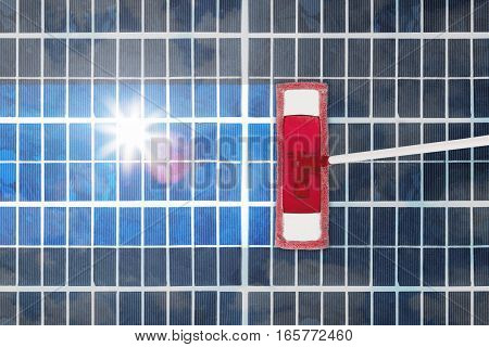 High Angle View Of Cleansing Tool On Shiny Solar Panel. Sustainable Energy Concept
