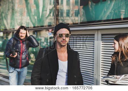 MILAN ITALY - JANUARY 17: Fashionable man poses outside Armani fashion show building during Milan Men's Fashion Week on JANUARY 17 2017 in Milan.
