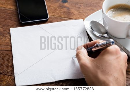High Angle View Of Person Hand Holding Pen On Blank White Paper On Wooden Desk