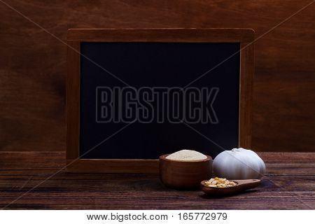 garlic cloves, bulb, flakes and powder on old wooden background with black board for text