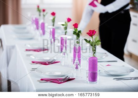 Male Waiter Placing Napkin On Wedding Table