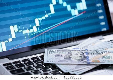 stock market graph on laptop screen and money. Trading concept