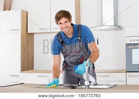 Happy Young Janitor Cleaning Kitchen Sink With Spray And Sponge