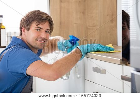 Happy Male Worker Holding Bottle Spray And Cleaning Countertop With Rag At Home