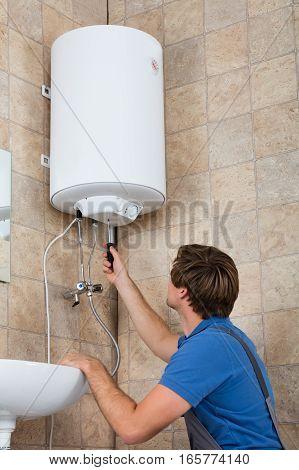 Technician Repairing Broken Electric Boiler At Home