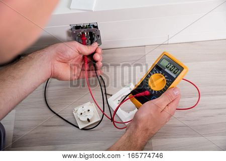 Close-up Of Person's Hand Holding Multimeter Checking Socket Voltage In A Wall Fixture