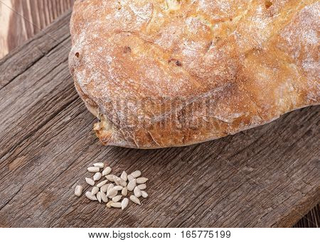 fresh homemade bread and sunflower kernels placed on a wooden table