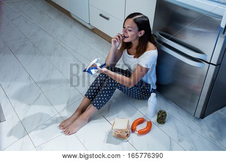 Woman Eating Chocolate While Sitting On Floor Near Sandwich And Jar Of Pickle In Kitchen