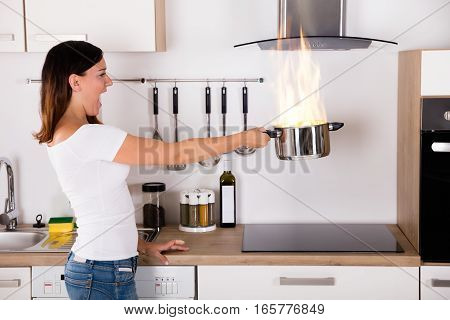 Shocked Young Woman Holding Cooking Pot With Fire Near Modern Gas In Kitchen
