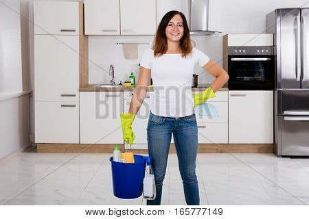 Young Happy Woman Using Cleaning Tools And Products In Bucket In Kitchen