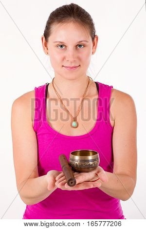young pretty woman holding a singing bowl in front of him. focus on girl