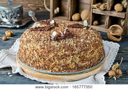 Sweet homemade honey cake with with walnuts and grated chocolate. Toned photo