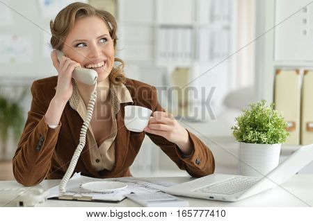 Portrait of young businesswoman talking on the phone in the office