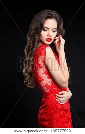 Beautiful Sexy Woman Posing In Red Dress Isolated On Black Background. Beauty Makeup. Long Healthy C