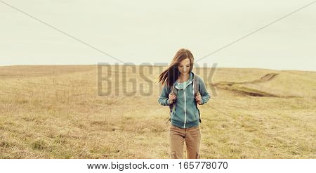 Backpacker young woman walking on spring meadow