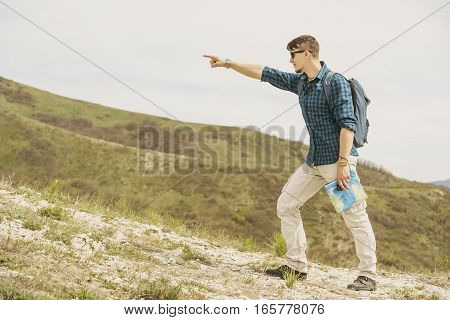 Backpacker young man with map walking in mountains and pointing into the distance. Space for text in left part of the image