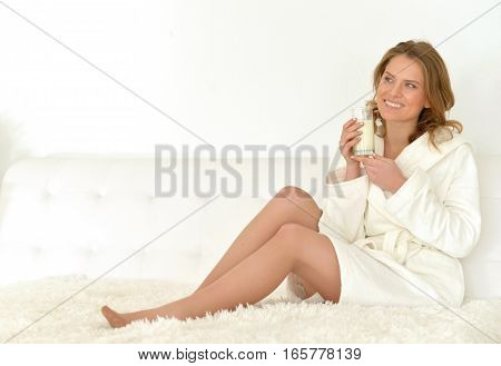 Beautiful woman in bathrobe sitting on bed and drinks milk