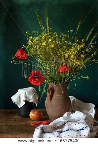 Still life with yellow wild flowers and poppy in vase