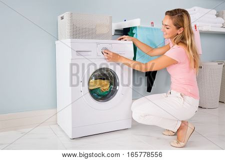 Young Smiling Woman Using Washing Machine To Clean Clothes In Laundry Room