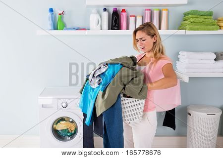 Young Unhappy Tired Woman Holding A Bucket Of Dirty Clothes In Laundry Room