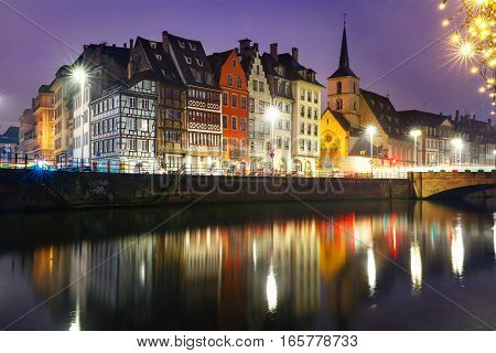 Picturesque quay and church of Saint Nicolas with mirror reflections in the river Ile and Christmas garland during morning blue hour, Strasbourg, Alsace, France
