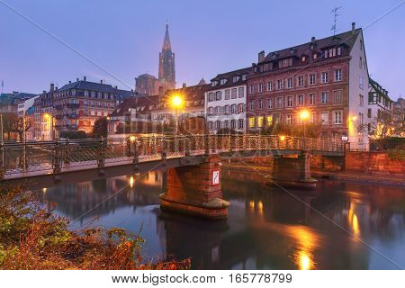 Picturesque landscape with bridge and river embankment Ile during morning blue hour, Strasbourg Cathedral in the background, Strasbourg, Alsace, France